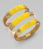 A set of three stunning bangles of natural horn, richly wrapped in brass wire and bright leather cord.Natural cow hornBrassLeatherDiameter, about 2¾Imported