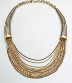 This unique statement piece features a mix of link and snake chains in a multi-row style with textured, horn-shaped endcaps. Antique-finished goldtoneLength, about 17Lobster clasp closureImported
